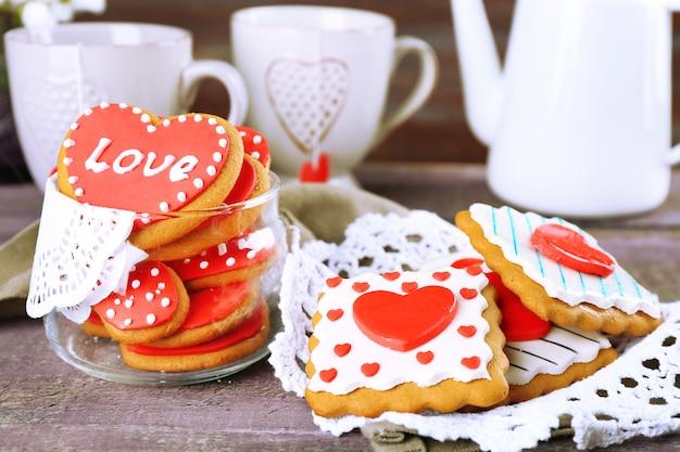 Ciasteczka w kształcie serca na walentynki, czajnik i filiżanki na kolorowym drewnianym tle