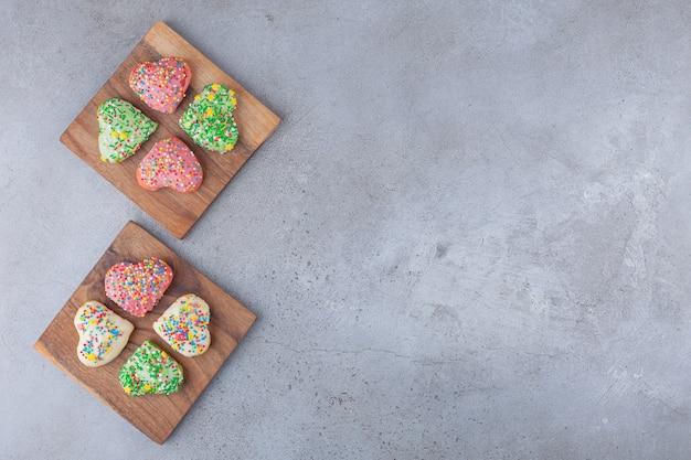 Ciasteczka w kształcie serca z kolorową posypką umieszczone na drewnianej desce.