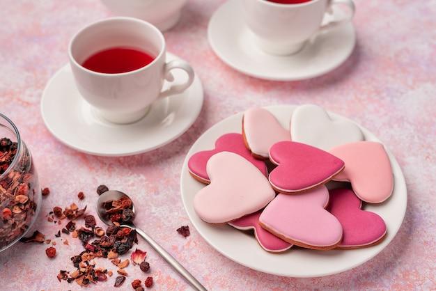 Ciasteczka w kształcie serca z polewą z herbatą jagodową. koncepcja: walentynkowa impreza z herbatą, świąteczny nakrycie stołu w kolorze różowym.