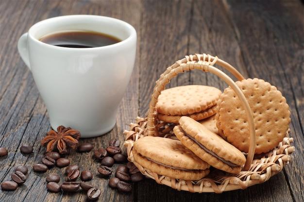Ciasteczka w wiklinowym koszu i filiżankę kawy na stole