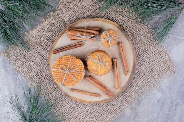 Ciasteczka waflowe na drewnianej desce z laskami cynamonu