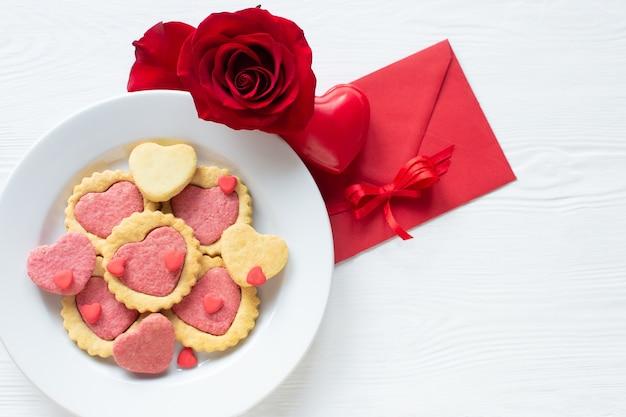 Ciasteczka walentynkowe na talerzu krok po kroku 5. czerwona róża, walentynka list i serce. pyszne domowe, naturalne organiczne ciasteczka w kształcie serca, wypieki z miłością na walentynki, koncepcja miłości.