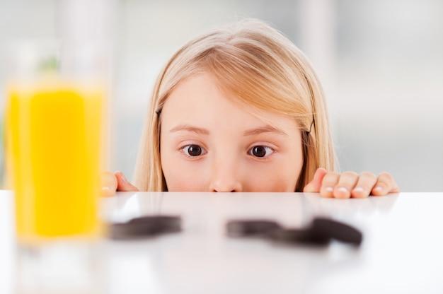 Ciasteczka! wesoła dziewczynka patrząca ze stołu z ciasteczkami i szklanką soku na nim