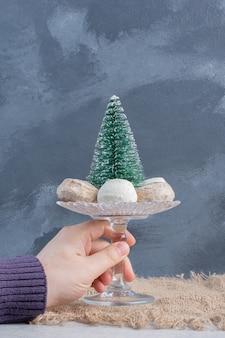 Ciasteczka wokół figurki drzewa na małym piedestale, trzymane ręką na marmurowej powierzchni