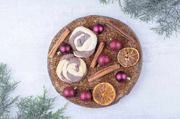Ciasteczka z bombkami, cynamonem i plasterkami pomarańczy na kawałku drewna