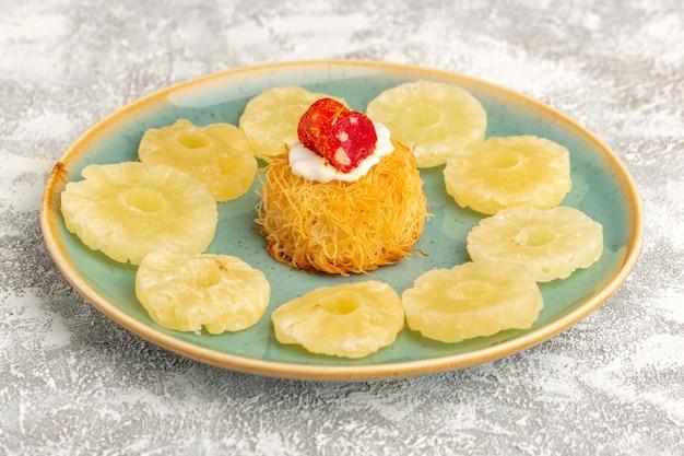Ciasteczka z ciasta wschodniego wewnątrz talerza z białymi kremowymi krążkami suszonego ananasa