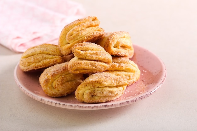 Ciasteczka z cynamonem i cukrem zwane gęsimi łapkami na talerzu
