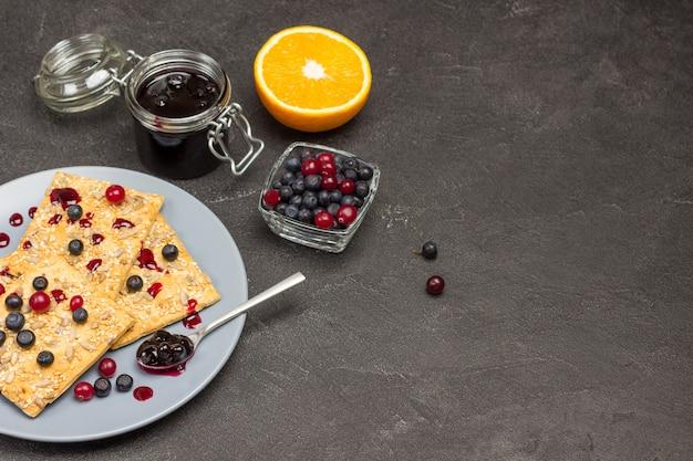 Ciasteczka z jagodami i łyżką z dżemem na szarym talerzu. pomarańczowa połówka na stole. słoik dżemu i jagody w misce. skopiuj miejsce. czarne tło. widok z góry