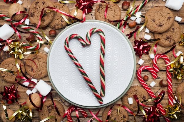 Ciasteczka z kawałkami czekolady świąteczne laski karmelu czerwone złoto dekoracje i ptasie mleczko na drewnianym pustym talerzu. copyspace frame.