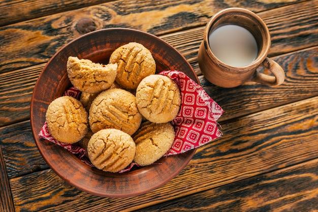 Ciasteczka z masłem orzechowym i gliniany kubek z mlekiem na drewnianym tle
