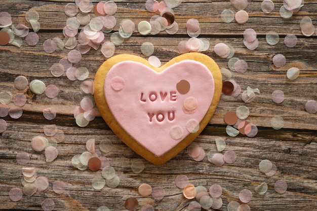 Ciasteczka z napisem kocham cię na tle drewna. tło wiosna. koncepcja miłości