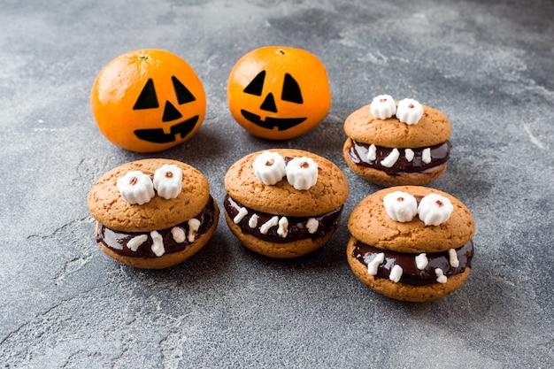 Ciasteczka z pastą czekoladową w postaci potworów i dyniowych mandarynek na halloween