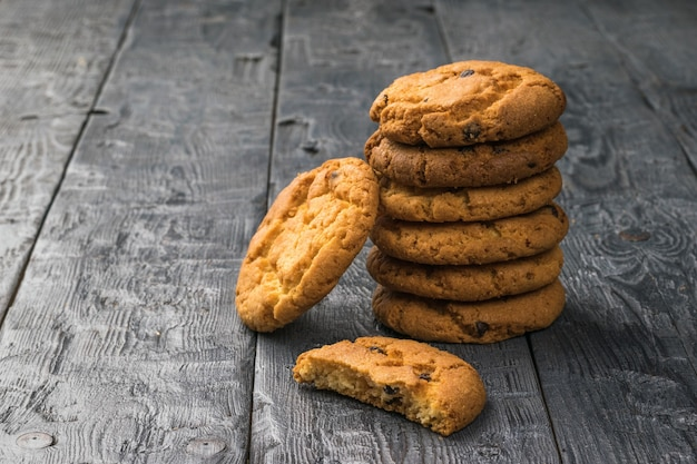 Ciasteczka Z Płatkami I Czekoladą Na Czarnym Drewnianym Stole Premium Zdjęcia