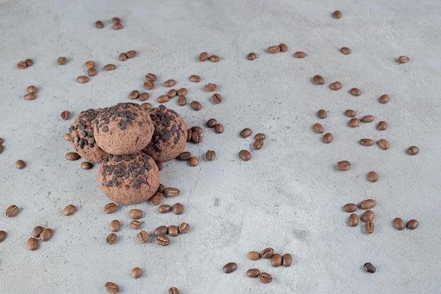 Ciasteczka z polewą czekoladową i rozsypanymi ziarnami kawy na marmurowym stole.