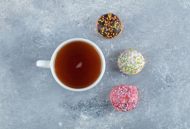 Ciasteczka z posypką i filiżankę herbaty na marmurowym stole.