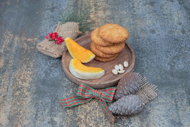 Ciasteczka z szyszkami i dwa plasterki dyni na drewnianym talerzu.
