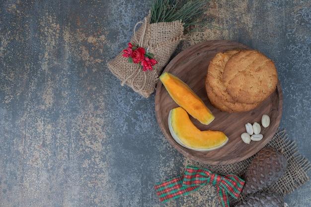 Ciasteczka z szyszkami i dwoma plasterkami dyni na drewnianym talerzu.