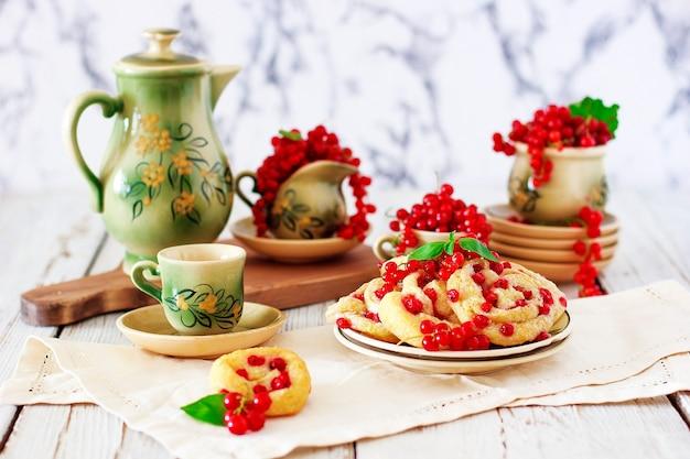 Ciasteczka z twarogiem z czerwonymi porzeczkami na talerzu ceramicznym z zestawem ceramicznych filiżanek lub herbaty, herbata, śniadanie, letnie słodycze