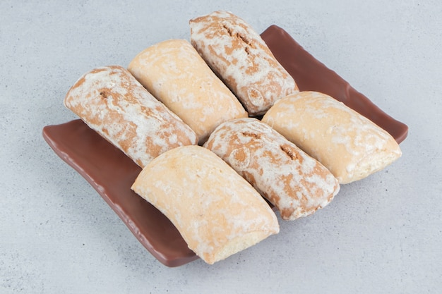 Ciasteczka zawijane na talerzu na marmurowym tle.