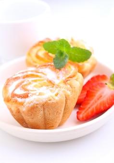 Ciastka biszkoptowe z nadzieniem twarogowym ozdobione truskawkami i miętą