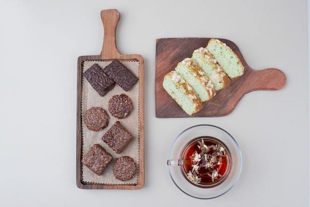 Ciastka czekoladowe, plastry ciasta pistacjowego i szklanka herbaty na białej powierzchni.