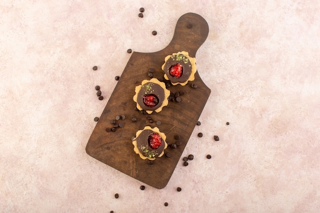 Ciastka czekoladowe z widokiem z góry na drewnianym biurku i różowym stole
