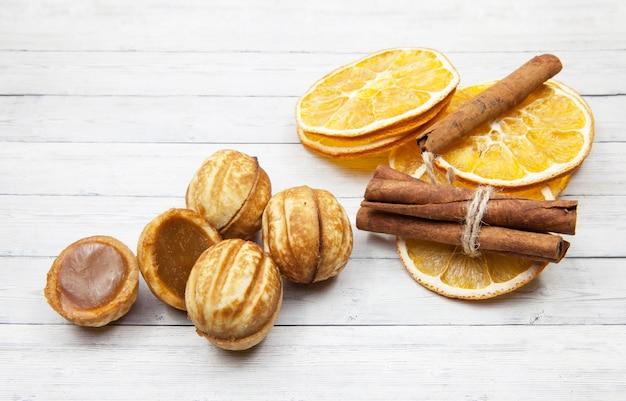 Ciastka - dokrętki i pomarańczowi plasterki z cynamonem na lekkim drewnianym tle