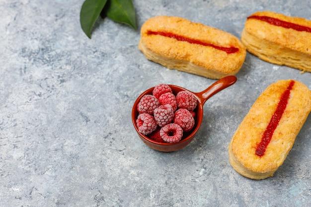 Ciastka francuskie z dżemem malinowym i mrożonymi malinami na świetle