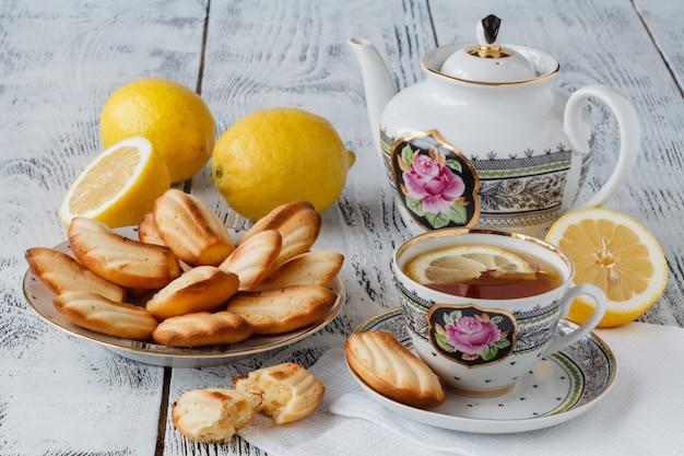 Ciastka herbaciane podawane w kwiatowym talerzu z filiżanką herbaty
