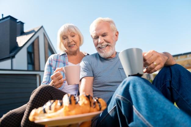 Ciastka i herbata. troskliwy, brodaty emeryt, mąż przy herbacie przynoszący ciastka dla pięknej żony