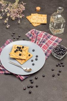 Ciastka i jagody na szarym talerzu na serwetce w kratkę. woda butelkowana. jagody w szklanej misce. łyżka jest na talerzu. czarne tło. widok z góry