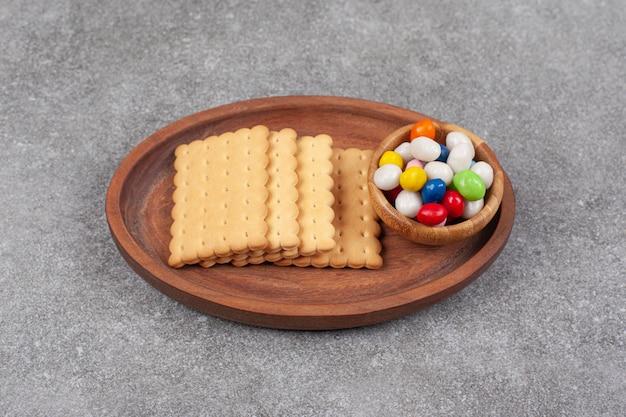 Ciastka i kolorowe cukierki na drewnianym talerzu
