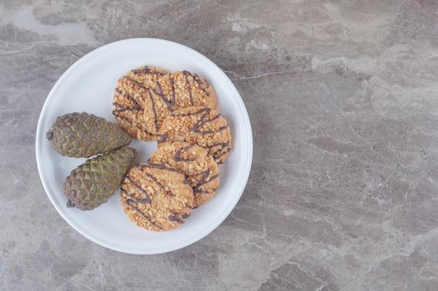 Ciastka i szyszki na talerzu na marmurze