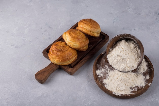 Ciastka lub bułeczki z mąką na drewnianym talerzu