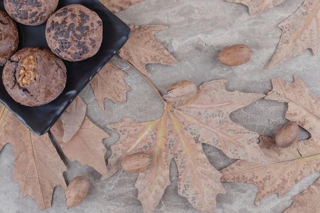 Ciastka na talerzu obok rozrzuconych liści platana i orzechów pekan na marmurze