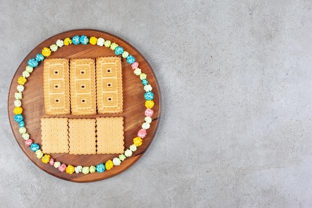 Ciastka otoczone popcornowymi cukierkami na drewnianej tacy na marmurowym tle. wysokiej jakości zdjęcie