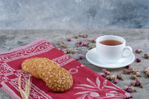 Ciastka owsiane i filiżanka czarnej herbaty na marmurowej powierzchni.