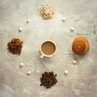 Ciastka, płatki owsiane, kawa, rodzynki i filiżanka herbaty z mlekiem. koncepcja zdrowego śniadania