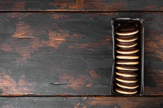 Ciastka ptasie ptasie czekoladowe, w pojemniku z tworzywa sztucznego, w pojemniku z tworzywa sztucznego, na starym ciemnym tle drewnianego stołu, widok z góry płasko leżał, z kopią miejsca na tekst