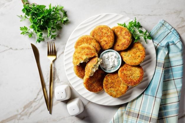 Ciastka rybne z fileta z dorsza lub łupacza z ziemniakami i natką pietruszki panierowane w bułce tartej na białym talerzu z sosem tatarskim w sosie na jasnym marmurowym tle kamienia, widok z góry, zbliżenie