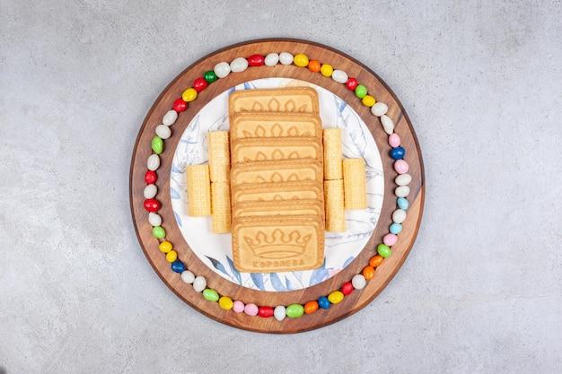 Ciastka ułożone na talerzu i otoczone cukierkami na drewnianej desce na marmurowym tle. wysokiej jakości zdjęcie