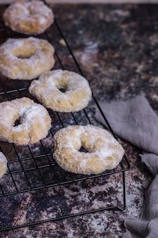 Ciastka w kształcie pierścienia nad rusztem piekarnika na ciemnej powierzchni