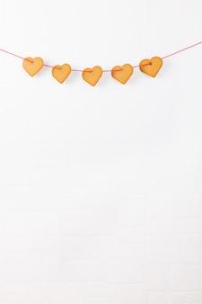 Ciastka w kształcie serca wisi na białej ścianie. symbol przytulnej miłości i walentynki tła i świąteczny koncepcji