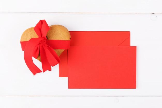 Ciastka w kształcie serca z czerwoną wstążką i czerwoną kartkę z życzeniami na białym tle. symbol przytulnej miłości i walentynki tło