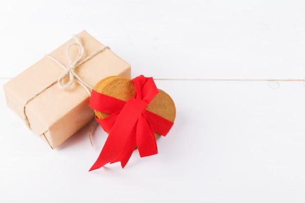 Ciastka w kształcie serca z czerwoną wstążką i prezentem rzemieślniczym, jadalny prezent na białym tle. symbol przytulnej miłości i walentynki tło