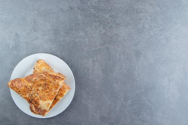 Ciastka w kształcie trójkąta wypełnione mięsem na białym talerzu.