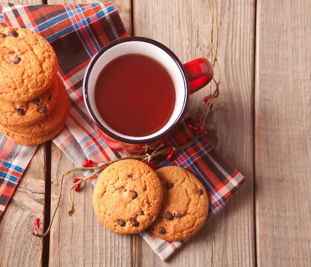 Ciastka z czerwonym kubkiem gorącej herbaty lub kawy na drewnianym stole