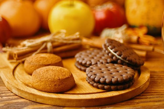 Ciastka z dyniami i jabłkami na stole. ciasteczka i jesienne dekoracje. dynie i jabłka