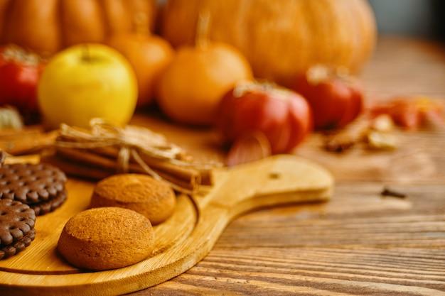 Ciastka z dyniami i jabłkami na stole.