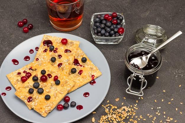 Ciastka z jagodami na szarym talerzu. nasiona słonecznika i siemię lniane na stole. słoik dżemu, szklanka herbaty i jagody w misce. czarne tło. widok z góry